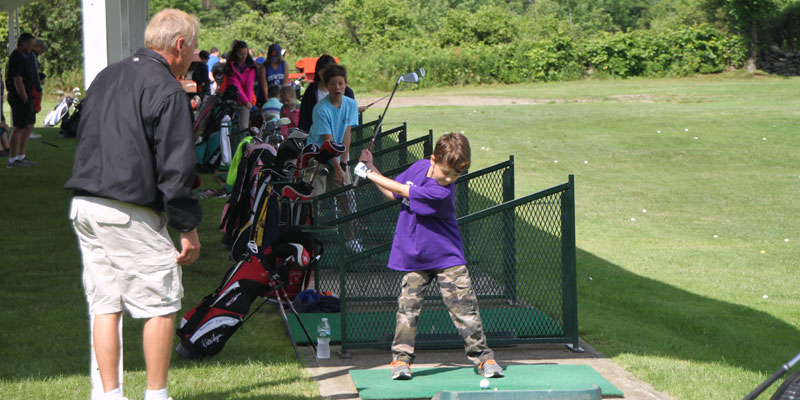 Photo of John Lawton giving golf lessons on the range at Junior Golf Camp.